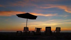 Asiento relajante al lado de la playa en puesta del sol Fotografía de archivo