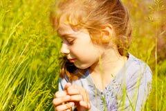 Asiento rubio de la muchacha del niño en un prado Foto de archivo