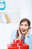 Asiento sonriente del operador en la tabla con la caja de regalo roja Negocio feliz Imágenes de archivo libres de regalías