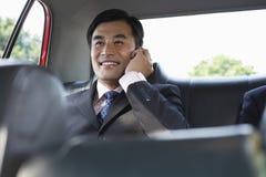 Asiento trasero de Using Cellphone In del hombre de negocios del coche fotos de archivo