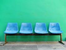 Asientos azules contra la pared verde. Foto de archivo libre de regalías
