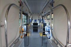 Asientos azules y grises para los pasajeros en salón del autobús vacío de la ciudad Foto de archivo