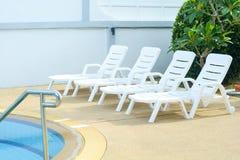 Asientos blancos en el borde de la piscina Foto de archivo libre de regalías