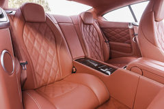 Asientos de pasajero traseros del rojo en coche cómodo de lujo moderno Fotos de archivo