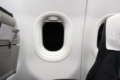 Asientos de un aeroplano, con una ventana en la noche Fotos de archivo libres de regalías