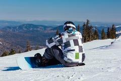 Asientos del Snowboarder en el top de la montaña Foto de archivo