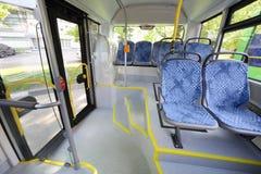 Asientos en el compartimiento de pasajero del autobús vacío de la ciudad Fotografía de archivo