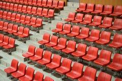 Asientos rojos del estadio de la vista lateral Imagenes de archivo