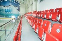 Asientos rojos en la arena de los hielo-deportes en Kranevo, Bulgaria Imagenes de archivo