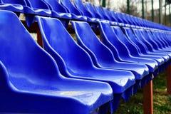 Asientos vacíos de los azules en la tierra de deportes al aire libre imagen de archivo libre de regalías