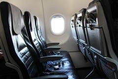 Asientos y correa de un aeroplano, con una ventana Fotos de archivo