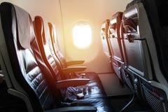 Asientos y correa de un aeroplano, con una ventana Imagenes de archivo