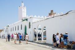 Asilah,摩洛哥- 2013年8月14日:走和购物在白色清真寺和城市墙壁前面的未认出的游人 免版税库存照片