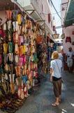 Asilah, Maroc - 14 août 2013 : Jeune femme non identifiée regardant beaucoup de chaussures en cuir à vendre dans la rue Photo libre de droits
