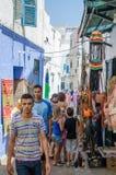 Asilah, Marruecos - 14 de agosto de 2013: Calles estrechas de Asilah con los recuerdos y los artes para la venta y la gente no id Fotos de archivo