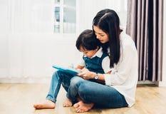 Asilo del figlio del ragazzo del bambino del bambino e bello disegno di insegnamento della madre insieme fotografia stock