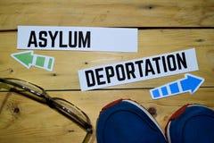 Asilo o deportazione di fronte ai segnali di direzione con le scarpe da tennis e gli occhiali su di legno immagini stock libere da diritti