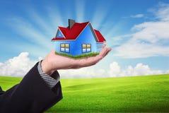 Asimiento de la mano una casa contra el cielo azul foto de archivo