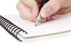 Asimiento de la mano una escritura de la pluma Imagen de archivo libre de regalías