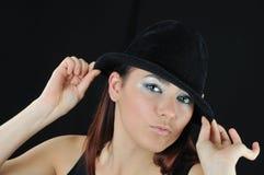 Asimiento de la muchacha en el sombrero imagenes de archivo