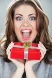 Asimiento de la mujer de la caja de regalo contra fondo gris foto de archivo