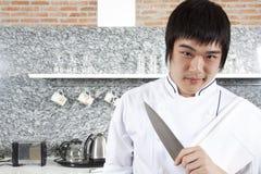 Asimiento del cocinero un cuchillo. Imágenes de archivo libres de regalías