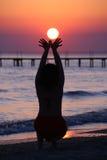 Asimientos de la muchacha lowing el sol. fotografía de archivo
