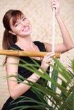 Asimientos felices de la mujer en la escalera de cuerda de bambú Imagenes de archivo