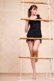 Asimientos hermosos de la mujer en la escalera de cuerda de bambú Foto de archivo libre de regalías