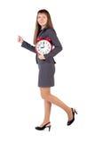 Asimientos jovenes de la empresaria en su reloj de alarma de las manos Imagen de archivo libre de regalías
