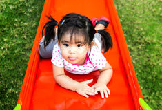 Asin girl playing slider at playground Stock Photos