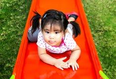 Asin-Mädchen, das Schieber am Spielplatz spielt stockfotos