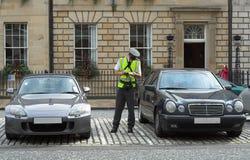 Asistente de estacionamiento, guarda del tráfico, consiguiendo el mandato de la multa del boleto Imagenes de archivo