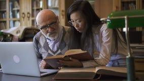 Asistente de investigación asiático femenino que muestra la página del libro al varón maduro metrajes