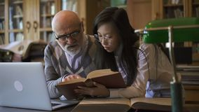 Asistente de investigación femenino asiático que trae el libro para madurar al profesor almacen de video