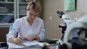 Asistente de investigación femenino profesional en la capa blanca que se sienta en la tabla con el microscopio y la calculadora d metrajes