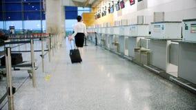 Asistente del enregistramiento de la línea aérea que camina con el equipaje 4k metrajes