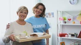 Asistente social que abraza la bandeja jubilada de la tenencia de la mujer con la comida, ofreciéndose voluntariamente visita almacen de metraje de vídeo