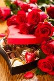 Ask av chokladtryfflar med röda rosor Arkivbild