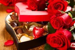 Ask av chokladtryfflar med röda rosor Royaltyfri Bild