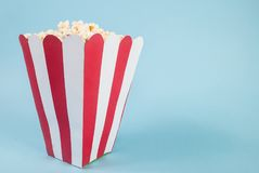 Ask av popcorn på blå bakgrund och utrymme för text arkivfoton