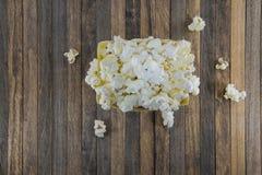 Ask av popcorn på en träbakgrund fotografering för bildbyråer