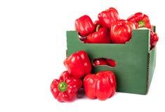 Ask av röda peppar som är klara till försäljningen som isoleras på vit bakgrund Arkivfoton