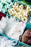 Ask av vita bomullsspets- och pompomband arkivbilder