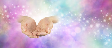 Ask Believe Receive. Pair of cupped palm up female hands on left side emerging from delicate bokeh sparkling background  with pale pastel coloring Stock Photo