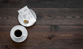 Ask for the bill at restaurant. Bill and coins near cup of coffee on wooden table top view copyspace Stock Image