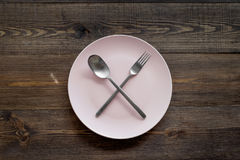 Ask for the bill at restaurant. Plate whith crossed spoon and fork on wooden table top view Stock Images