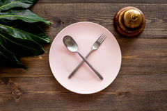 Ask for the bill at restaurant. Service bell near plate whith crossed spoon and fork on wooden table top view Stock Photo