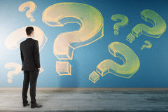 Ask concept. Back view of young businessman in interior looking at wall with drawn question marks. Ask concept royalty free stock photos