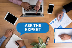ASK THE EXPERT. Business team hands at work with financial reports and a laptop, top view Royalty Free Stock Photos